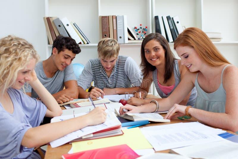 Adolescents de sourire étudiant dans la bibliothèque photo stock