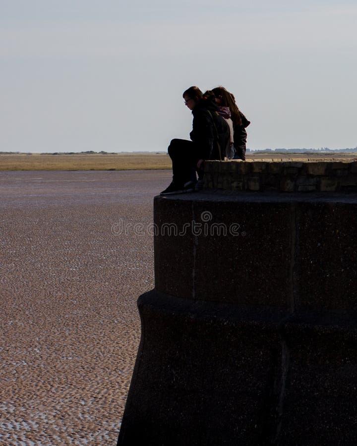 Adolescents en silhouette se reposant placé sur un mur de mer photo libre de droits