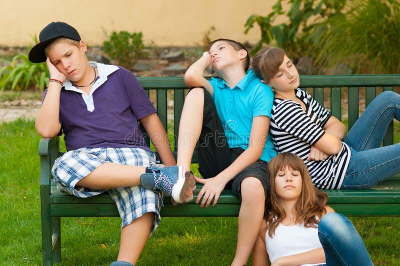Adolescents et filles se reposant sur le banc photos stock