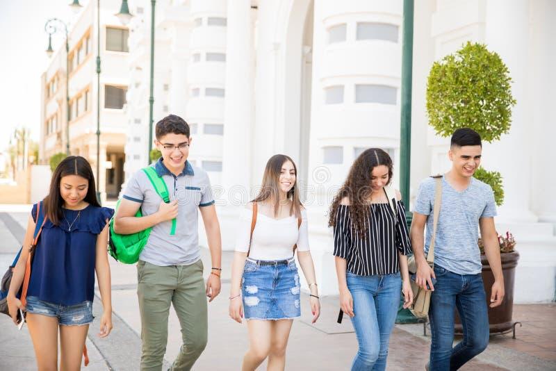 Adolescents heureux allant à l'école image stock