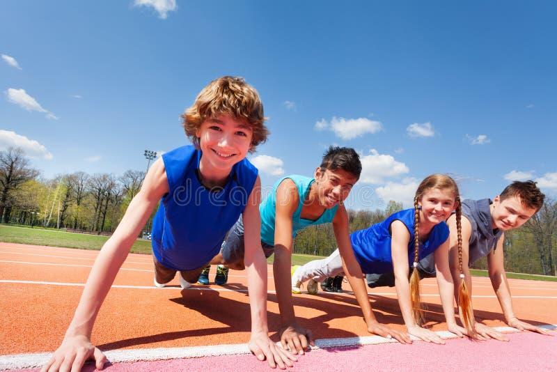 Adolescents heureux jugeant la planche extérieure sur la voie photographie stock libre de droits