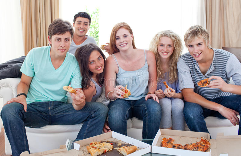 Adolescents heureux mangeant de la pizza dans la salle de séjour photos libres de droits