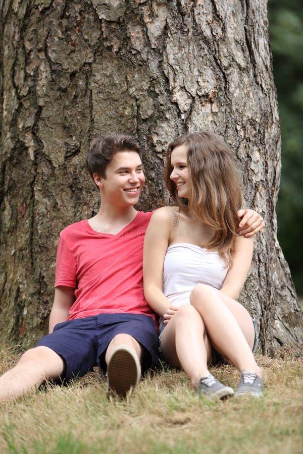 Adolescents heureux s'asseyant à la base d'un arbre photographie stock