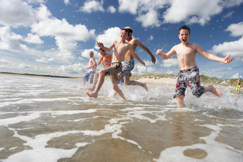 Adolescents jouant sur la plage image stock