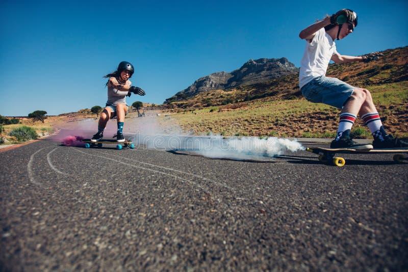 Adolescents longboarding sur la route ouverte images libres de droits