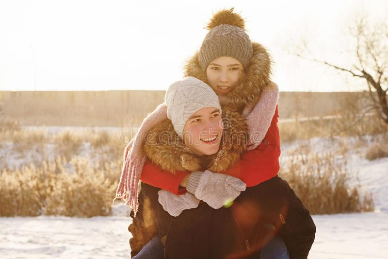 Teenagers in love. Date in winter. Adolescents in love on a date in winter. Man holding his girlfriend piggyback. Joy of being together. First love. Concept for stock photos