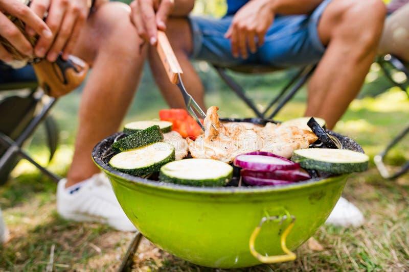 Adolescents méconnaissables faisant cuire des légumes sur le gril de barbecue photographie stock