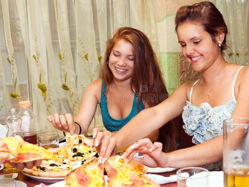 Adolescents mangeant de la pizza dans le restaurant photographie stock libre de droits