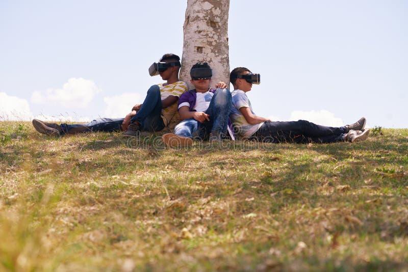 Adolescents noirs et blancs jouant la réalité virtuelle en parc photo stock