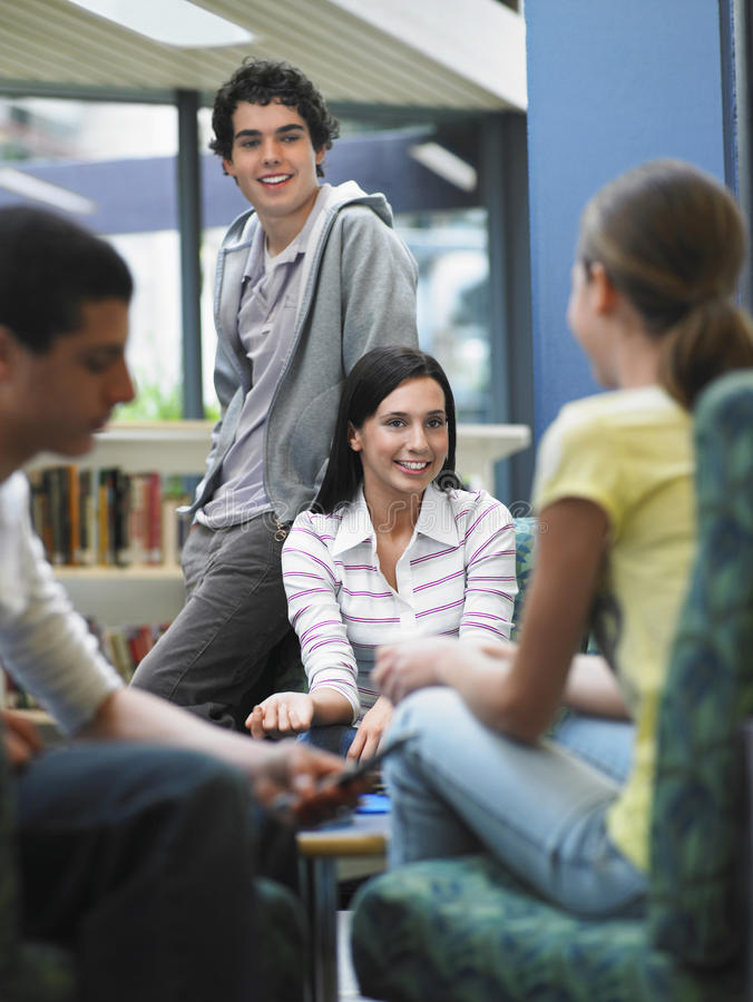 Adolescents parlant dans la bibliothèque images libres de droits