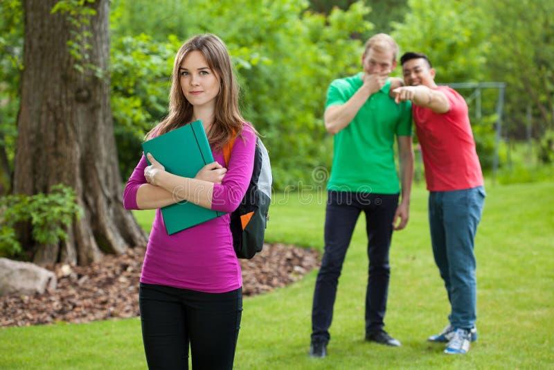Adolescents riant derrière le dos de la fille images stock