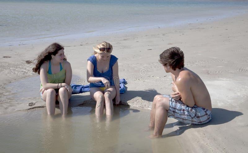 adolescents s'asseyants trois de plage photographie stock
