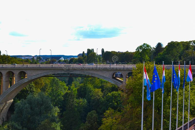 Adolphe Bridge Pont Adolphe i den Luxembourg staden, Luxembourg, med gröna träd och flaggor av Luxembourg och Europa på fotografering för bildbyråer