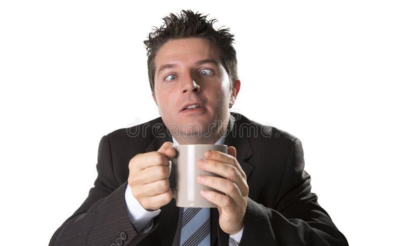 Adonnez-vous à l'homme d'affaires dans le costume et attachez tenir la tasse de café comme fou dans la dépendance de caféine photo stock