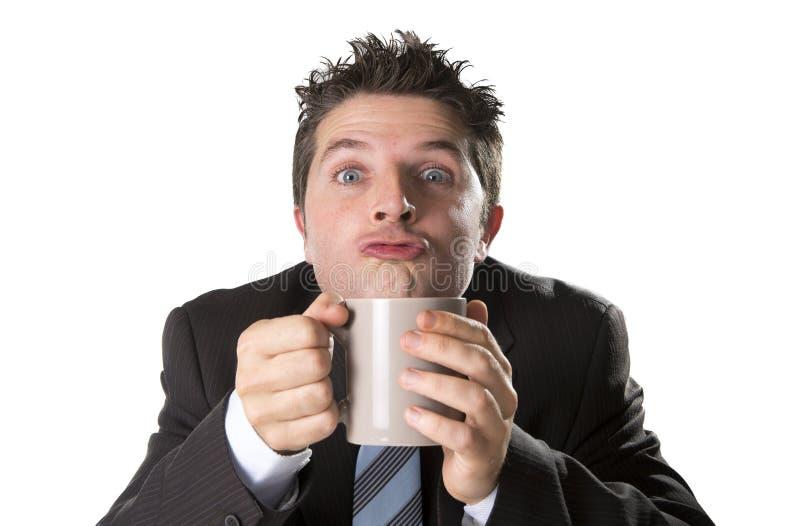 Adonnez-vous à l'homme d'affaires dans le costume et attachez tenir la tasse de café comme fou dans la dépendance de caféine image libre de droits