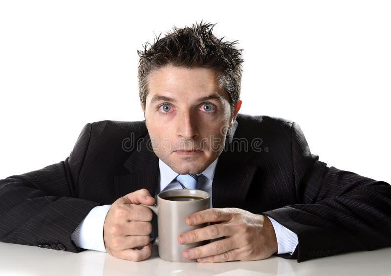 Adonnez-vous à l'homme d'affaires jugeant la tasse de café soucieuse et folle dans la dépendance de caféine images libres de droits