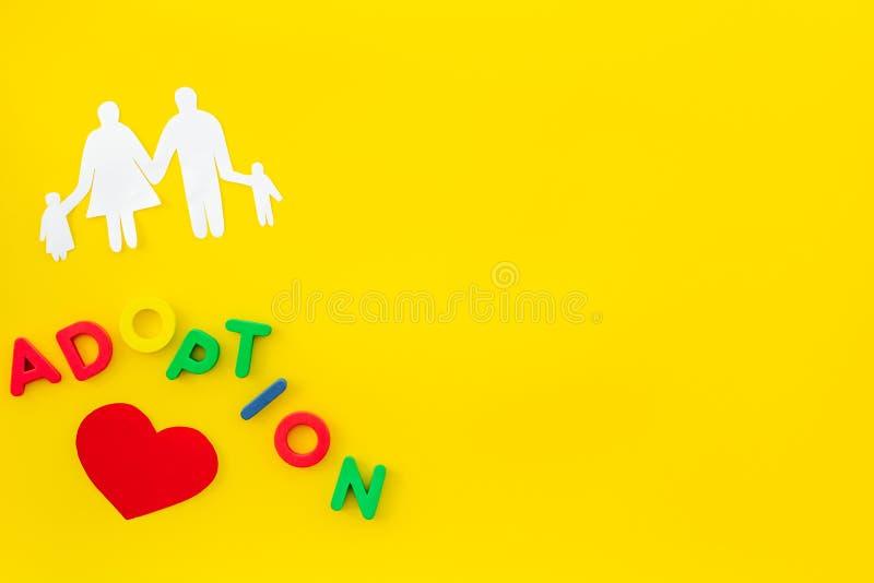 Adopcji postacie na żółtym tło odgórnego widoku copyspace i kopia fotografia royalty free