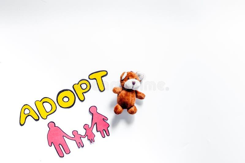 Adopte la palabra, la silueta de papel de la familia y los juguetes en el copyspace blanco de la opinión superior del fondo fotografía de archivo