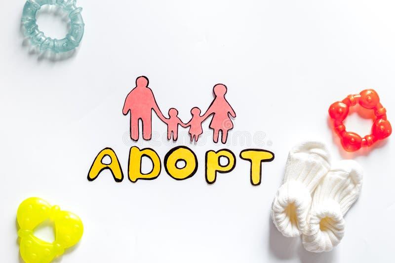 Adoptez le mot, la silhouette de papier de la famille et les jouets sur le copyspace blanc de vue supérieure de fond photos stock