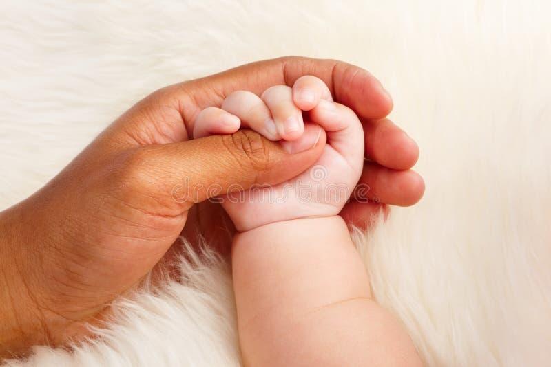 Adoption. Concept where dark skin parent holding hand of asian baby