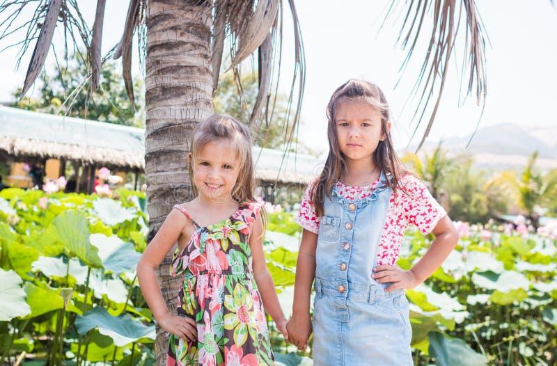 Adoráveis são duas meninas que estão ao lado de uma grande palma, de um sorriso e de um furados imagem de stock royalty free