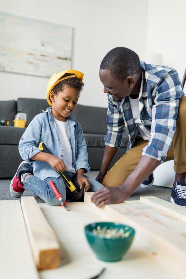 Adorável pai e filho africano-americano com martelo foto de stock royalty free