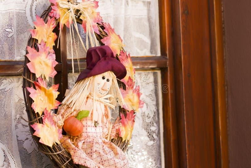 Adorabile figurina Happy Scarecrow tra una corona di foglie d'autunno colorate fotografia stock libera da diritti