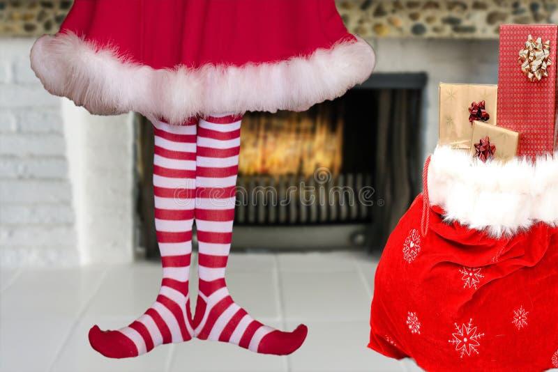Adorabile sveglio poca ragazza dell'elfo di natale con i piedi appuntiti che indossano le calze a strisce dell'elfo e una condizi fotografia stock