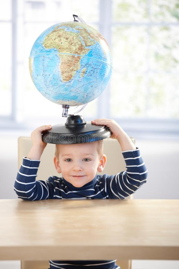 Adorable 3 year old having fun with globe smiling stock photo