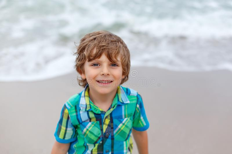 Adorable active little kid boy having fun on beach of North Sea in Germany. Happy cute child relaxing, playing and. Portrait of happy little kid boy on the beach stock photography