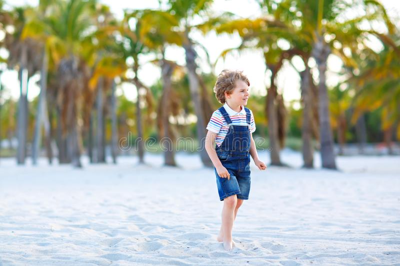 Adorable active little kid boy having fun on tropical beach of island. Happy cute child relaxing, playing, enjoying stock image