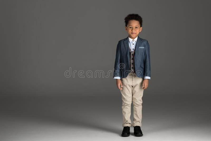 adorable african american boy standing in suit stock photo