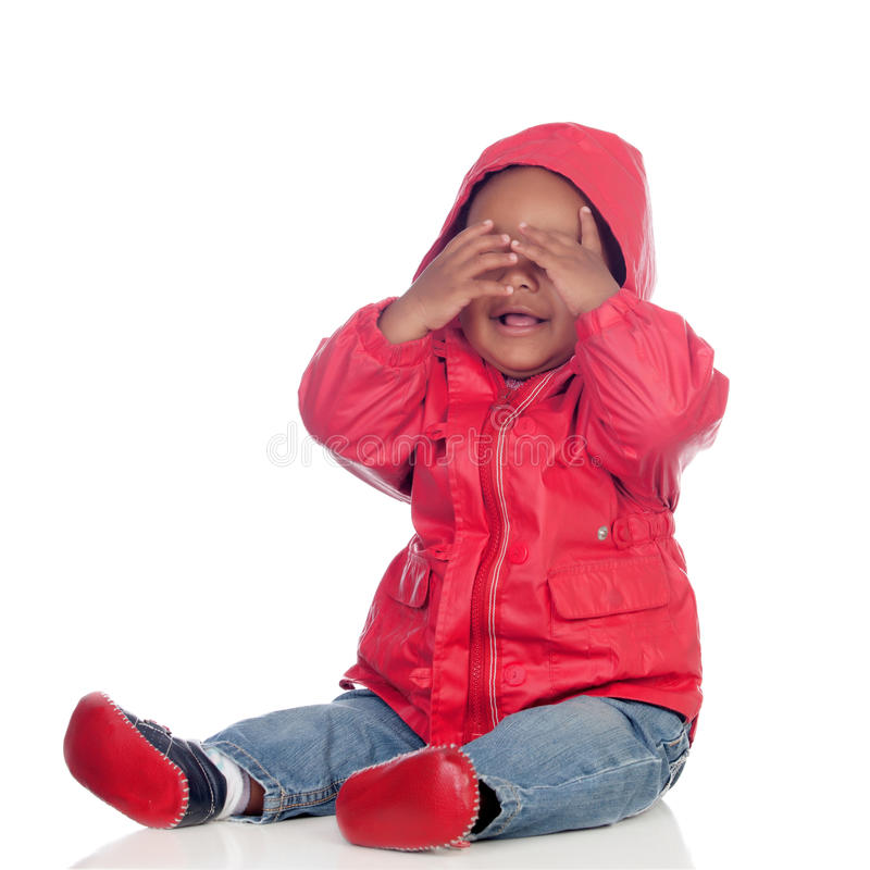 Adorable african baby sitting on the floor with red raincoat covering the face stock images