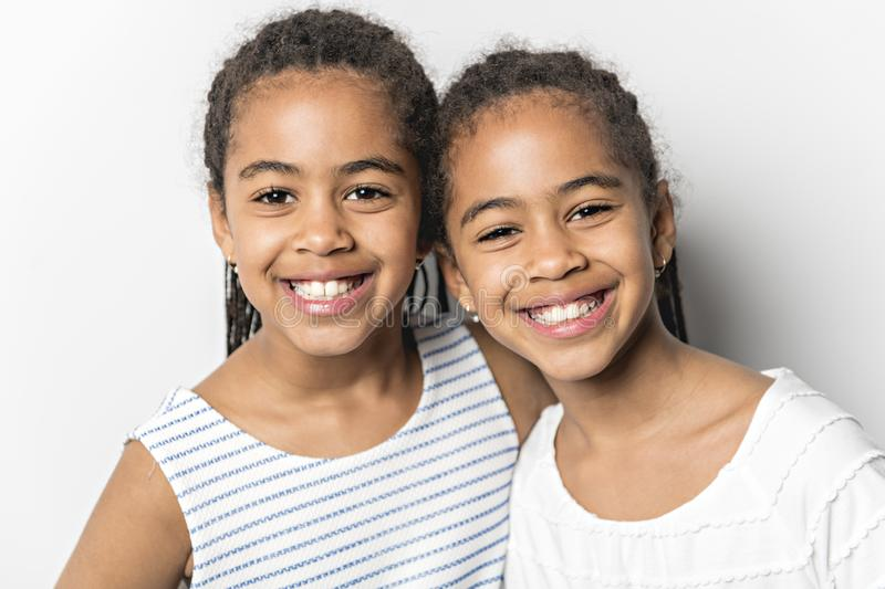 Adorable african twin little girls on studio gray background stock photography