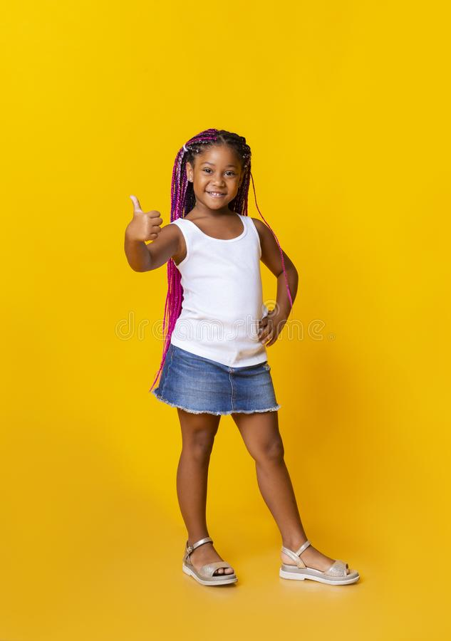 Adorable afro girl gesturing thumbs up on yellow studio background royalty free stock photo