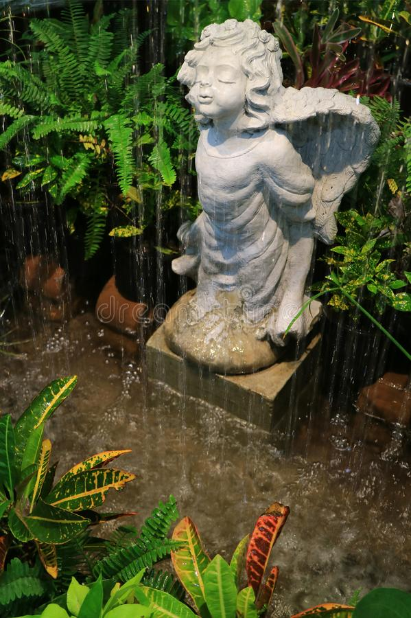 Adorable angel sculpture in the garden fountain, surrounded by Ferns and many tropical plants royalty free stock photo