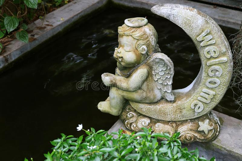 Adorable angel sitting on a crescent moon welcome sculpture at the garden pond side stock image