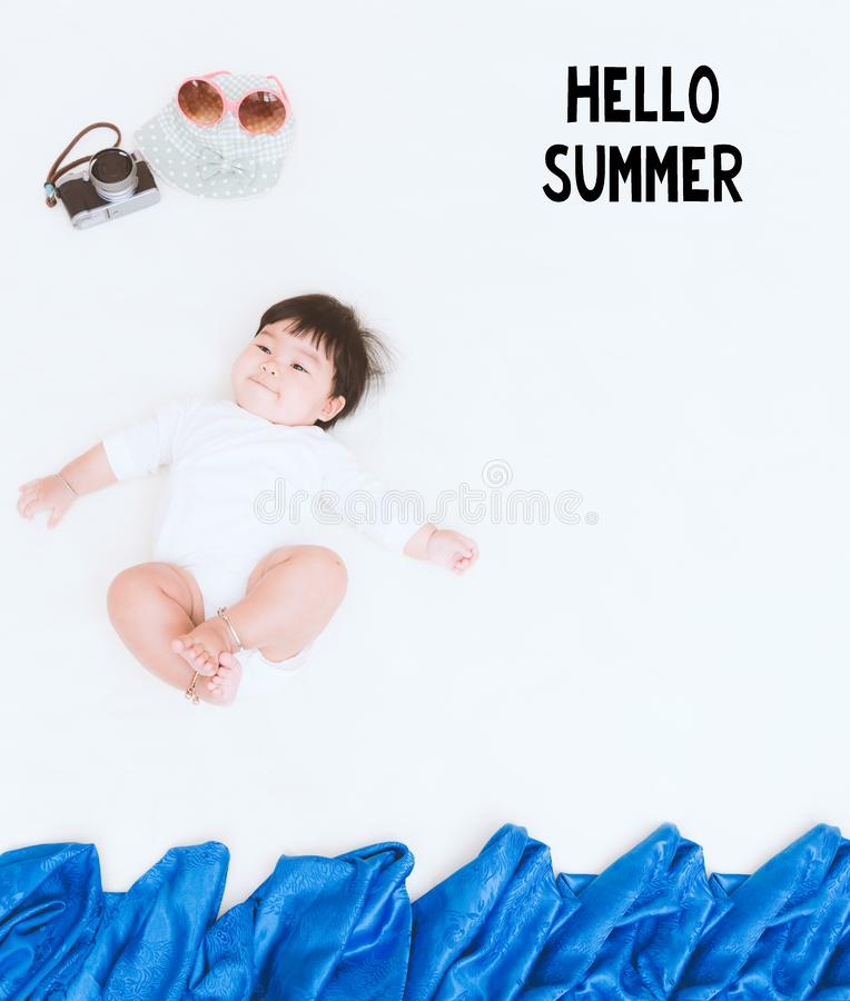 Adorable asian baby girl lie on the blanket with HELLO SUMMER message. stock images
