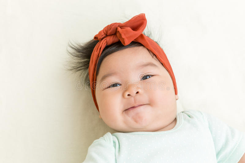 Adorable asian baby smiling on the bed. stock photos