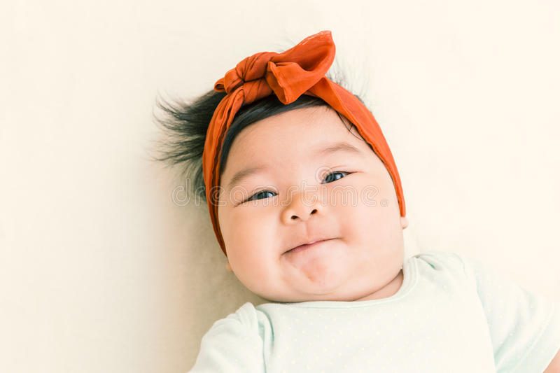 Adorable asian baby smiling on the bed. stock image