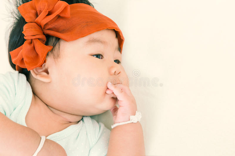 Adorable asian baby sucking thump on the bed. stock photos