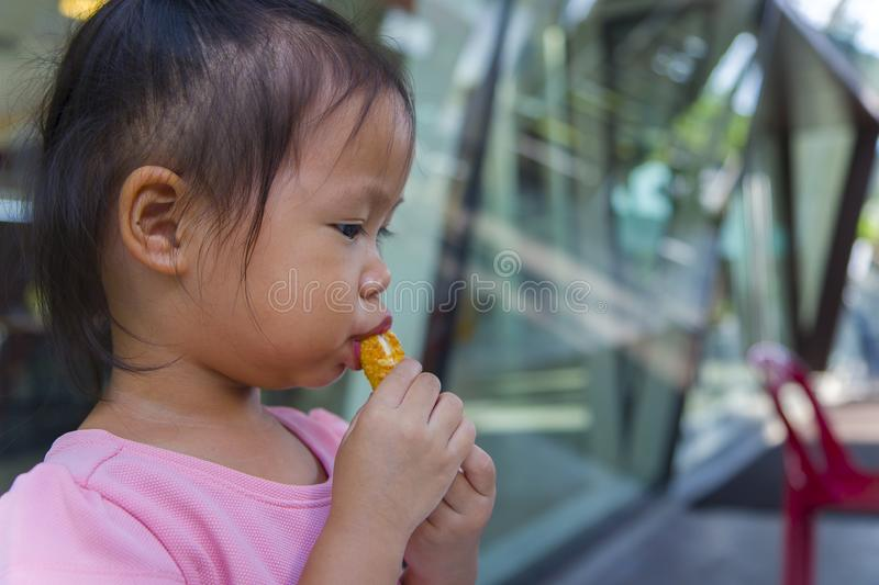 Adorable asian child smiling and enjoy eating breaded sticks at restaurant in her lunch. High resolution image gallery royalty free stock photography