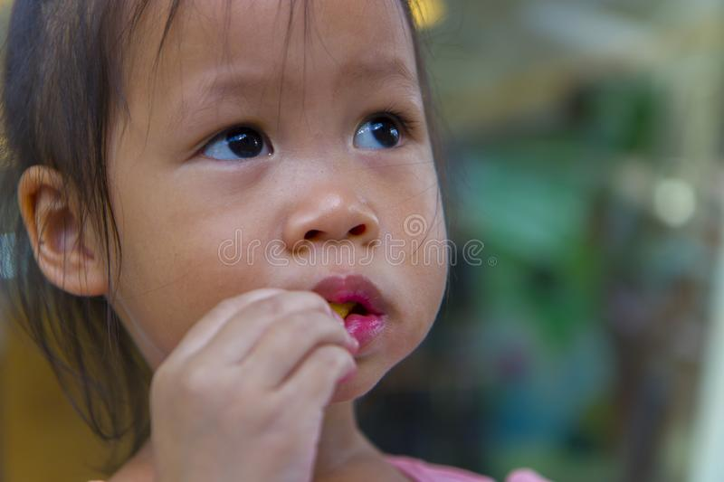 Adorable asian child smiling and enjoy eating breaded sticks at restaurant in her lunch. High resolution image gallery royalty free stock image