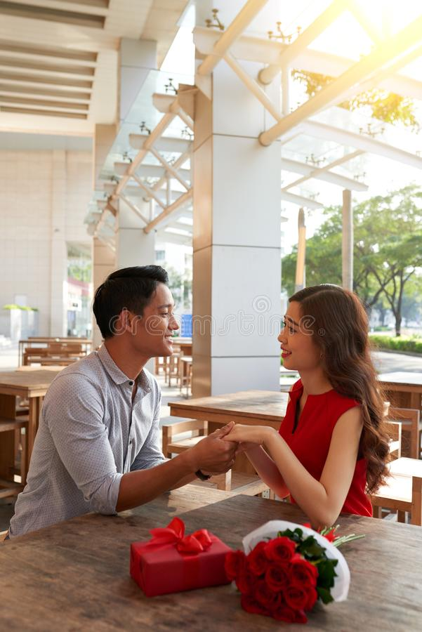 Adorable Asian couple. Looking at each other with wide smiles and holding hands while celebrating Valentines Day at outdoor cafe, bouquet of red roses and gift royalty free stock photography