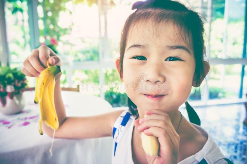 Adorable asian girl eating a ripe banana. vintage tone. royalty free stock photography