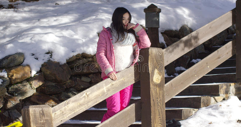 Adorable asian girl standing on wooden stairs stock image
