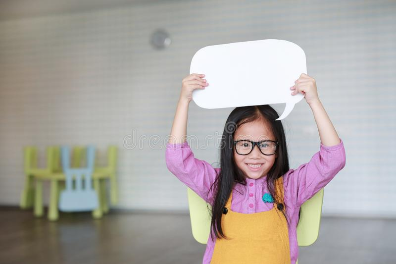 Adorable Asian little girl holding empty blank speech bubble to say something in the classroom with smiling and looking straight. At camera. Education and stock photography