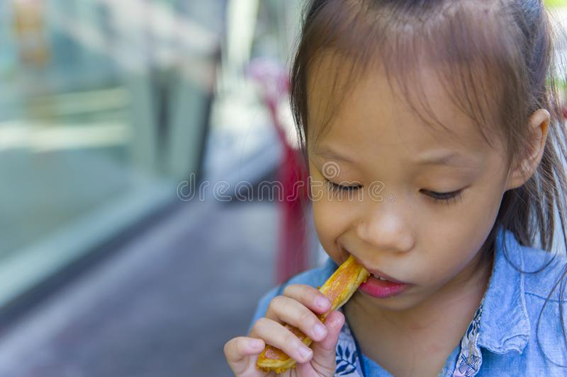 Adorable asian long hair boy smiling and enjoy eating breaded sticks at restaurant in his lunch. High resolution image gallery royalty free stock photos