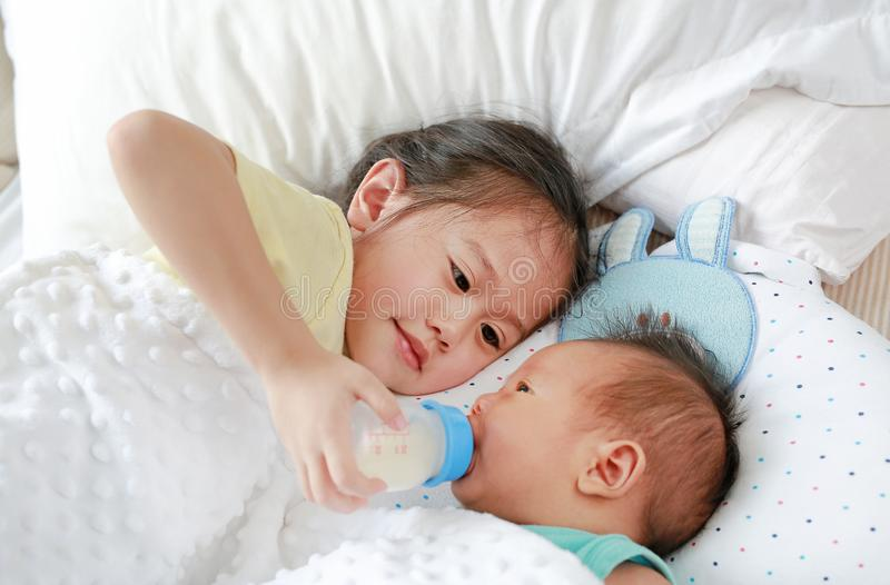 Adorable Asian older sister feeding milk from bottle for newborn baby lying on the bed stock photos