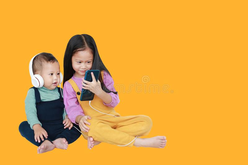 Adorable Asian older sister and little brother sharing to enjoys listening music with headphones by smartphone isolated over. Yellow background with copy space stock photo